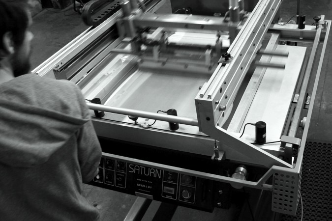 Custom Poster Printing on Semi-Automatic Flatstock Press at Triple Stamp Press in Richmond, VA. Photograph of Co-Owner Wil Loyal.